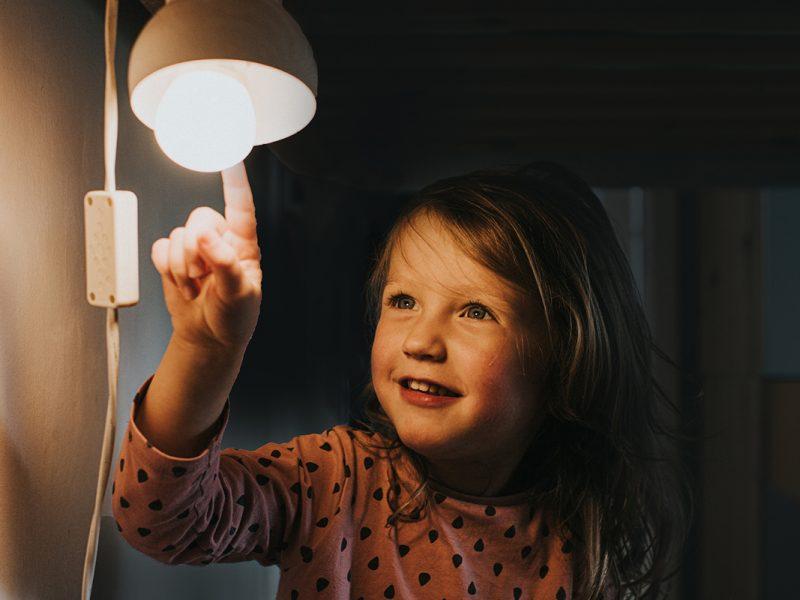 Kleines Mädchen berührt eine Glühbirne mit dem der Fingerspitze.