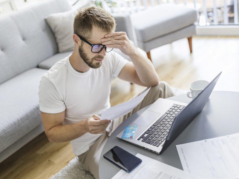 Mann arbeitet mit Notebook im Wohnzimmer
