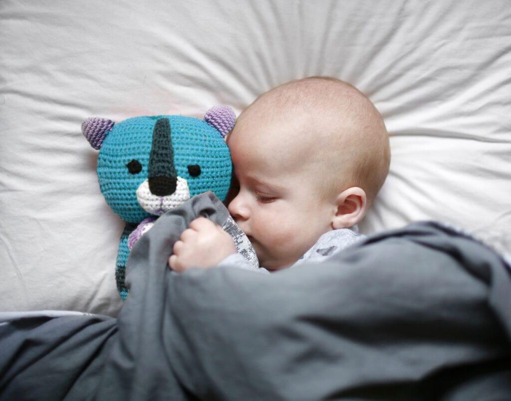 Schlafendes Baby mit Kuscheltier in Bett