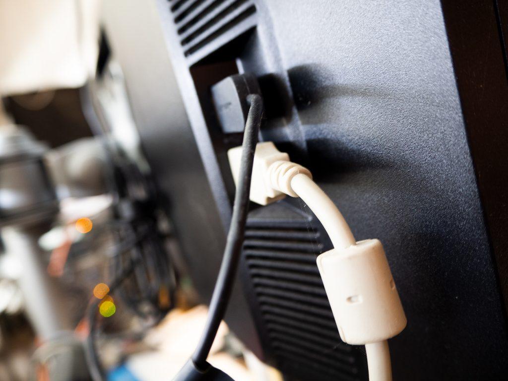 Schwarzer Monitor von hinten mit schwarzem und weißem Kabel