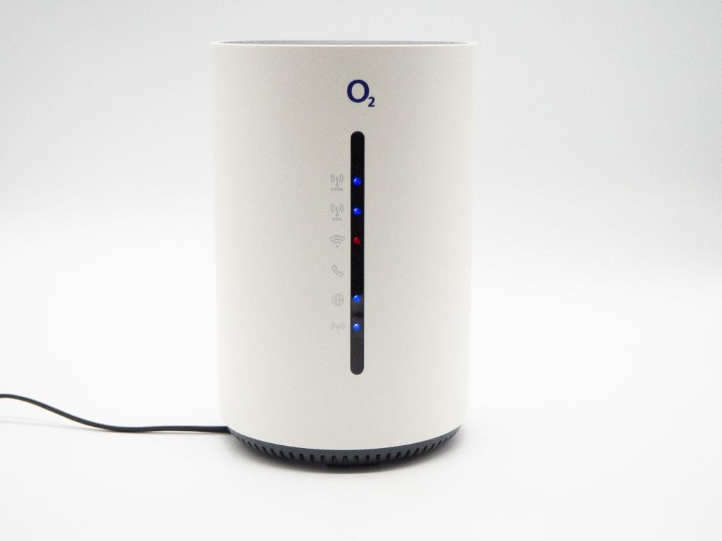 Weißes zylinderförmiges Gerät von o2 mit schwarzem Kabel vor grauem Hintergrund