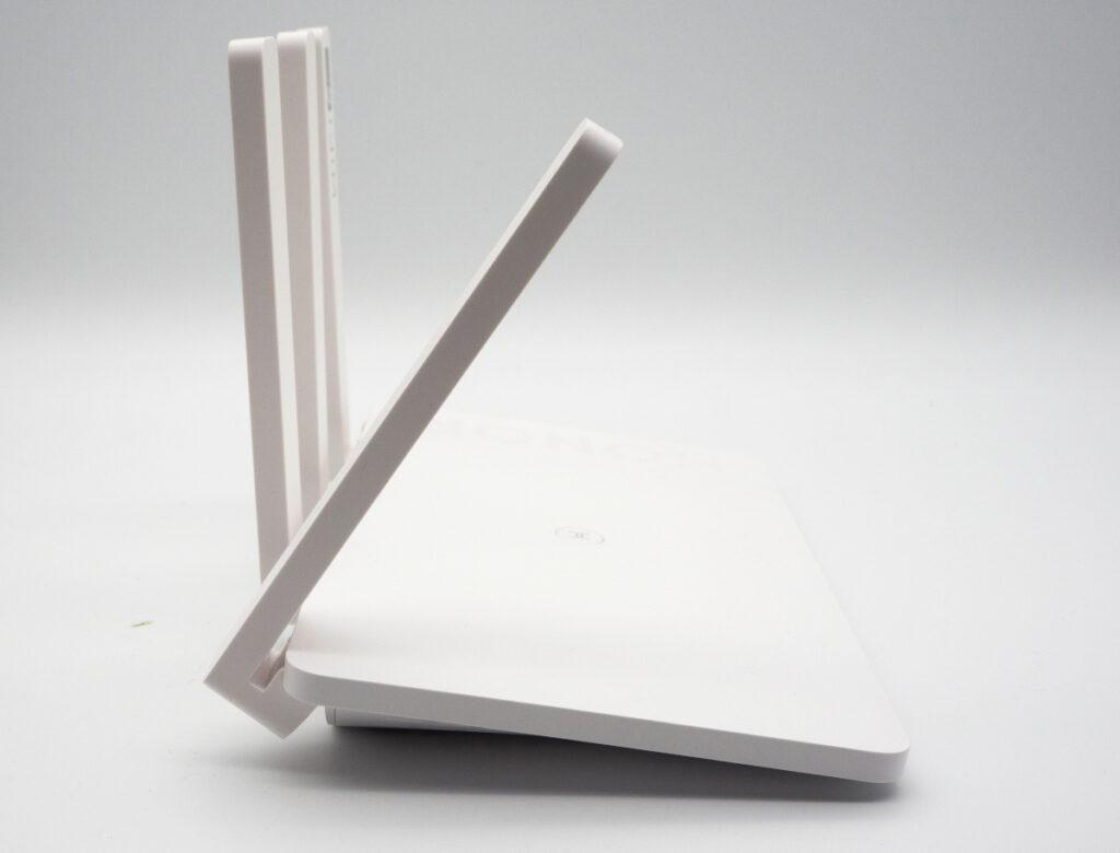 Weißer schlanker Router von der Seite mit drei langen Antennen an der linken Seite von der die vorderste nach vorne gerichtet ist