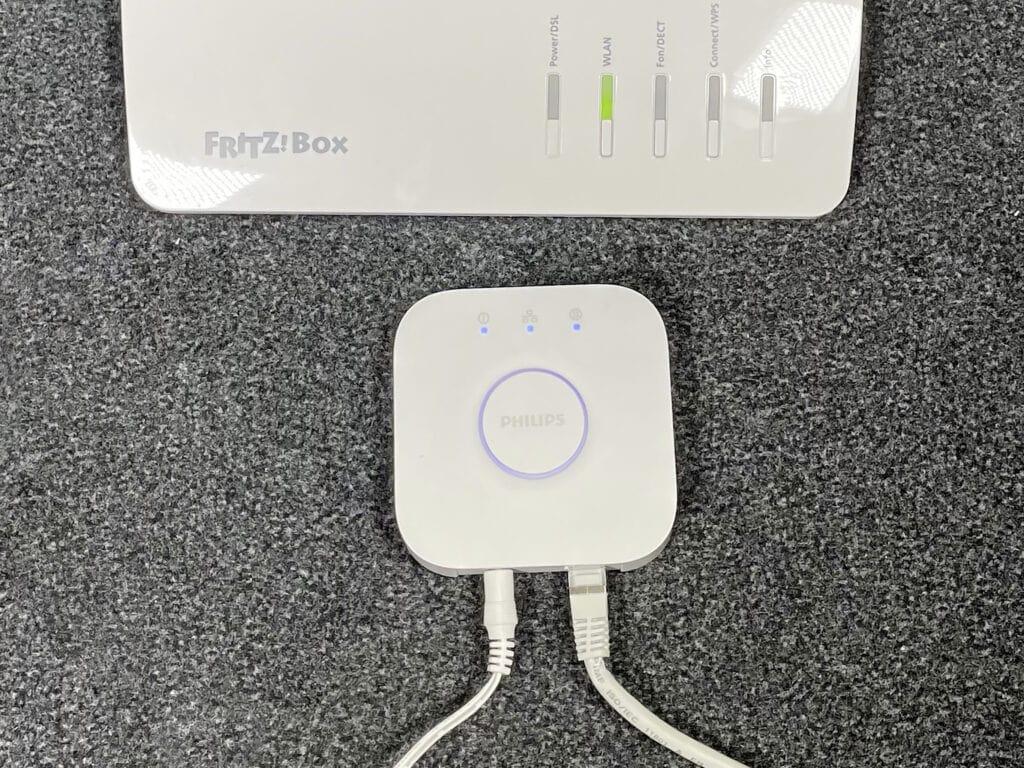 Weißes quadratisches Gerät mit zwei Kabeln vor weißem rechteckigen Router auf grauem Teppichboden