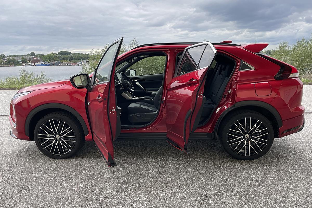 Rotes Auto von der Seite mit geöffneten Türen auf Parkplatz