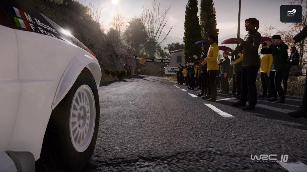 Screenshot mit links Kotfügel im Bild, fährt auf Straße mit Publikum rechts