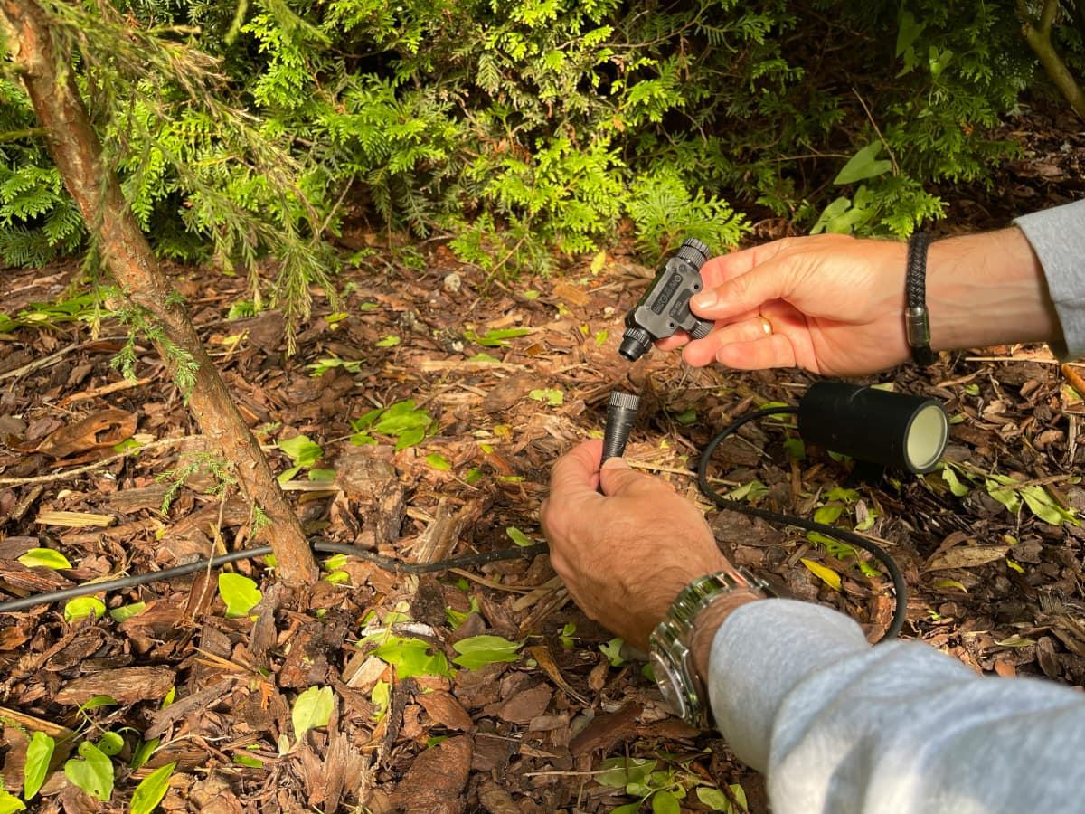 Zwei Hände halten Schraubverschlüsse auf Gartenboden