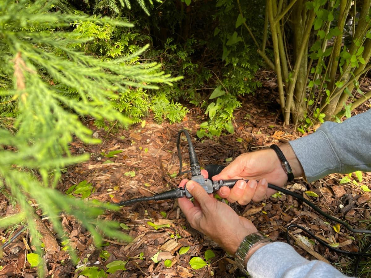 Zwei Hände schrauben Verbindungsstück und Kabel zusammen auf Gartenboden