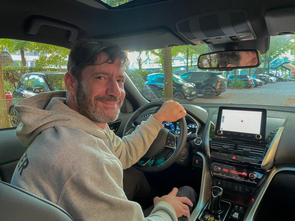 Mann in grauem Hoodie sitzt am Steuer und schaut lächelnd über die Schulter in die Kamera