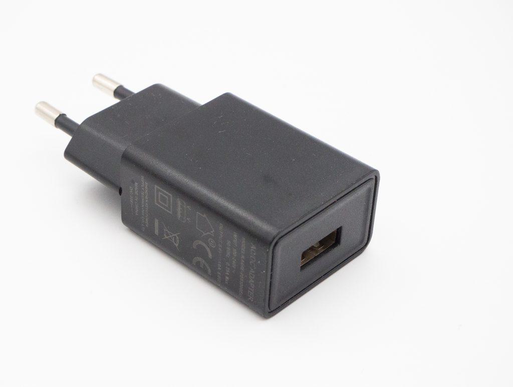 Schwarzer Stecker mit USB-Anschluss auf weißem Hintergrund