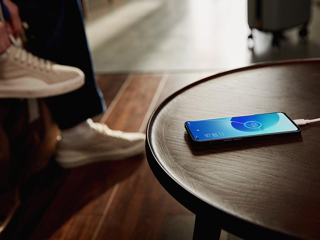 Smartphone liegt zum Laden auf einem Tisch vor dem eine Person sitzt