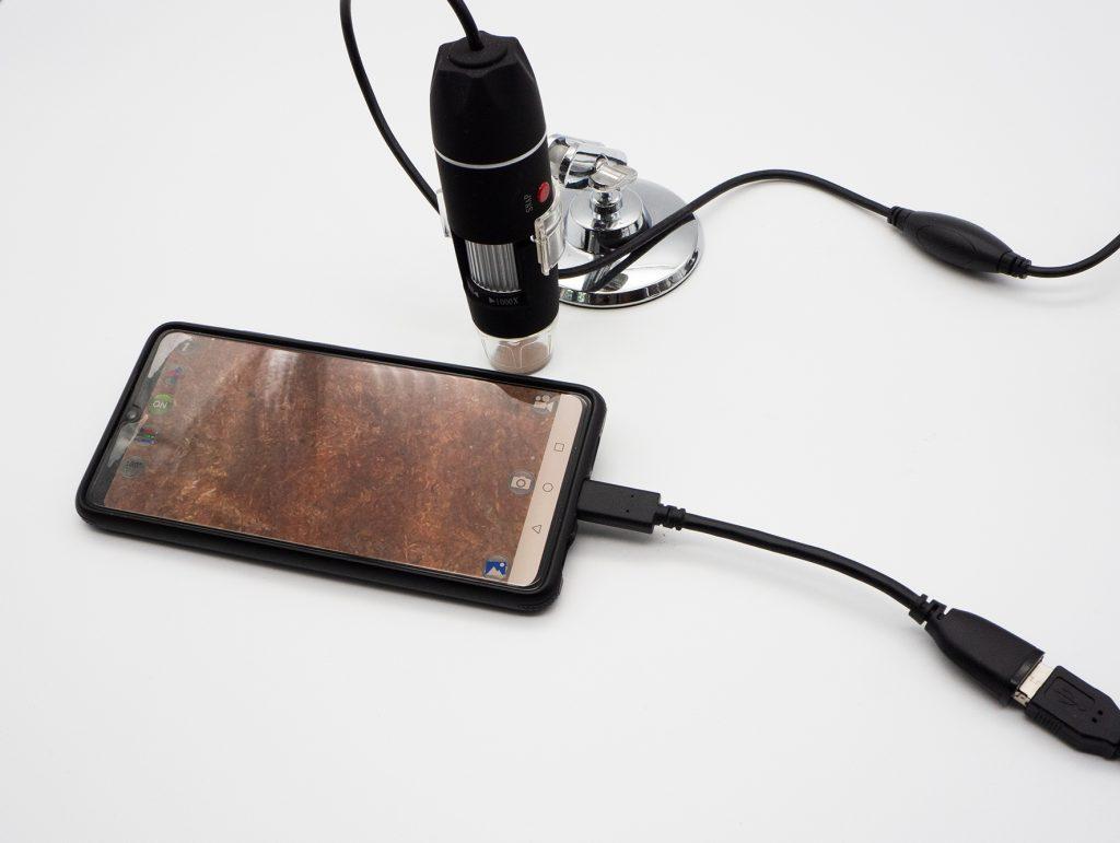 Schwarzes Smartphone mit schwarzem Kabel und kleinem schwarzen mikroskop mit schwarzem Kabel