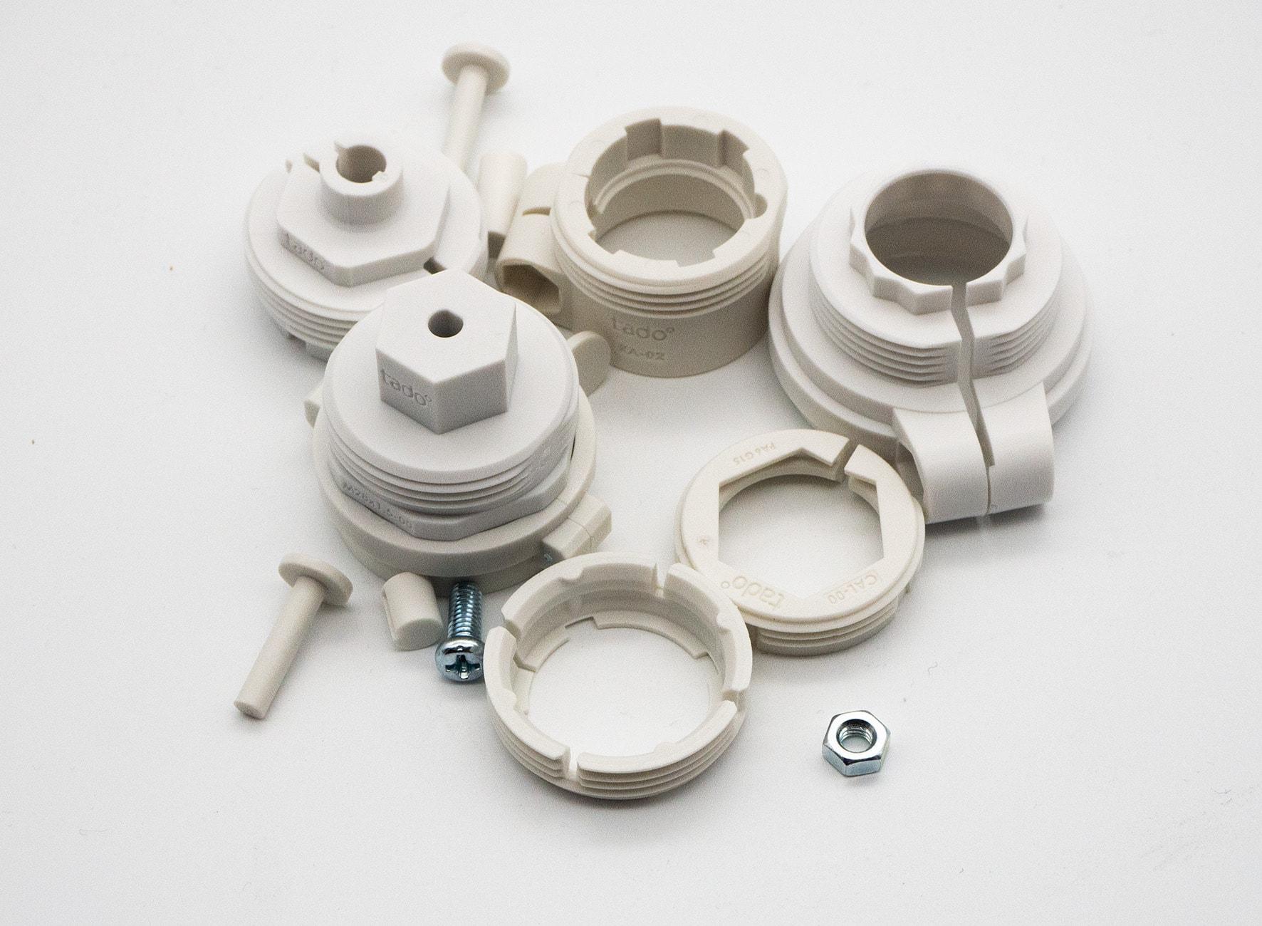 Unterschiedliche weiße runde Adapter liegen unsortiert auf weißem Boden