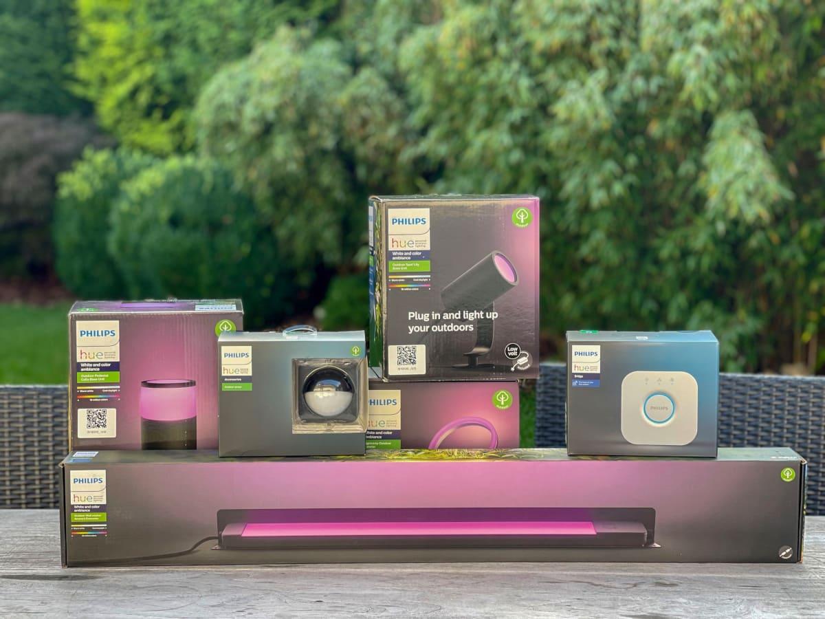 Verschiedene eingepackte Leuchten von Philipsauf grauem Tisch platziert vor grünen Büschen