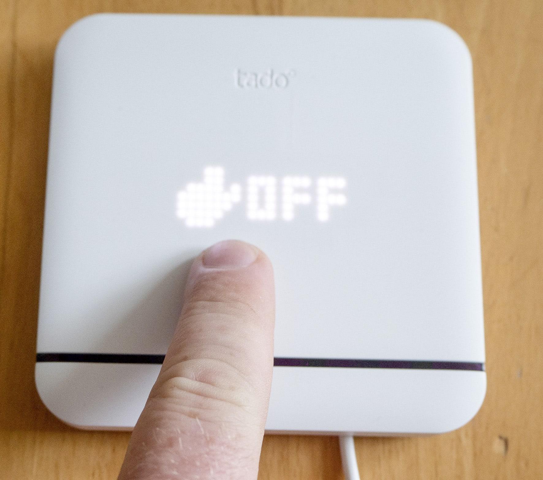 Finger tippt auf quadratisches, weißes Gerät mit der Anzeige Off, auf Holztisch