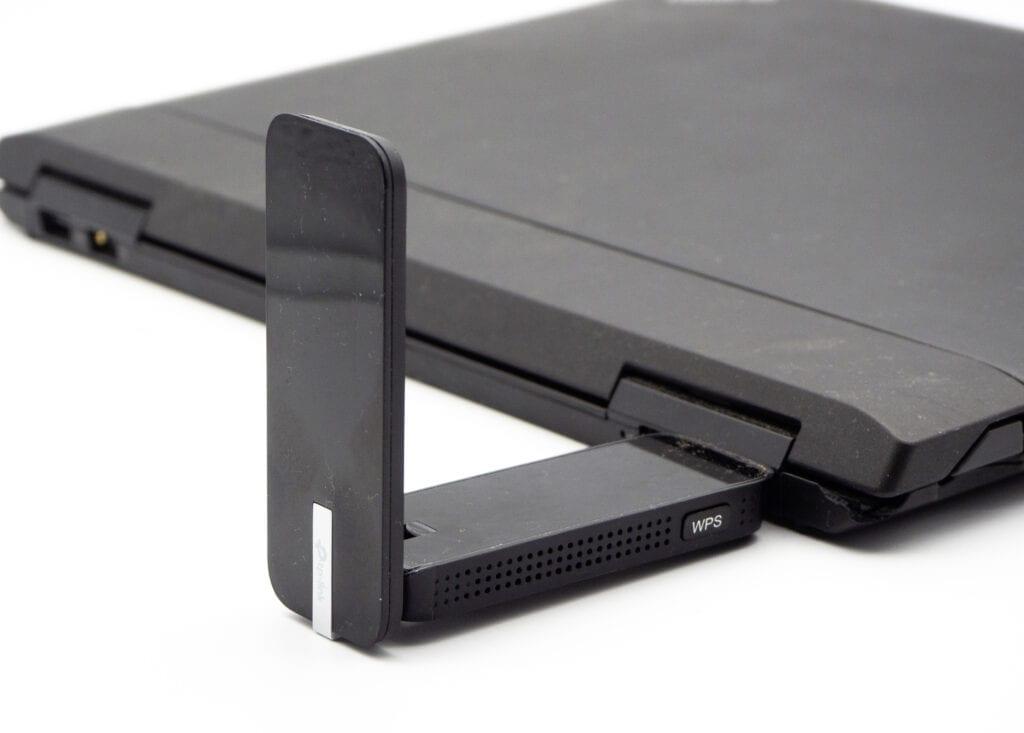 Zugeklapptes schwarzes Notebook von der Seite mit schwarzem rechtwinkelig abstehendem USB-Stick