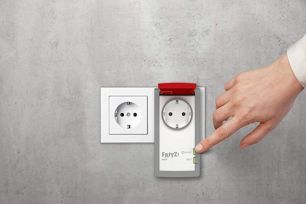 Graue Wand mit weißer freier Steckdose, daneben längliche Steckdose mit roter aufgeklappter Klappe, Hand die an der Steckdose einen Knopf drückt