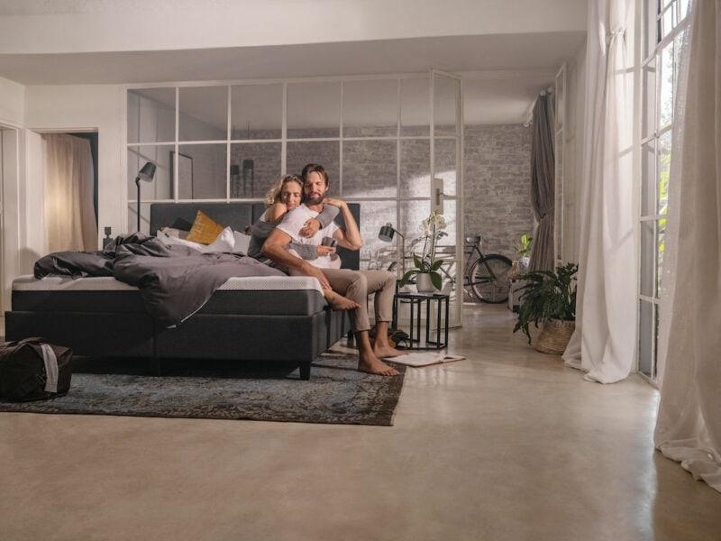 Ein Mann und eine Frau sitzen auf einem Bett