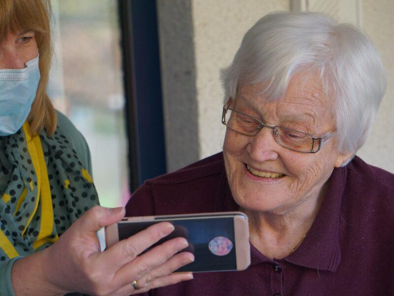 Eine ältere Dame schaut auf ein Smartphone.