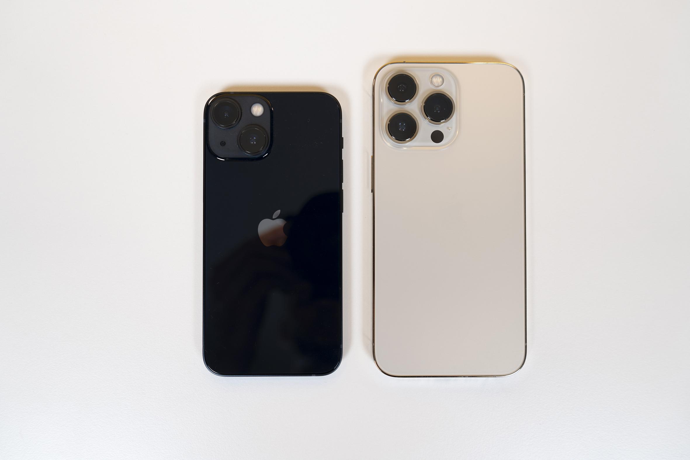 Schwarzes kleineres iPhone neben größerem hellem modell auf weißem Hintergrund