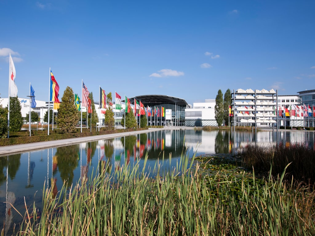 Großes langes Wasserbecken mit verschiedenen Fahnenmasten auf der linken Seite und dem Messegebäude in München im Hintergrund