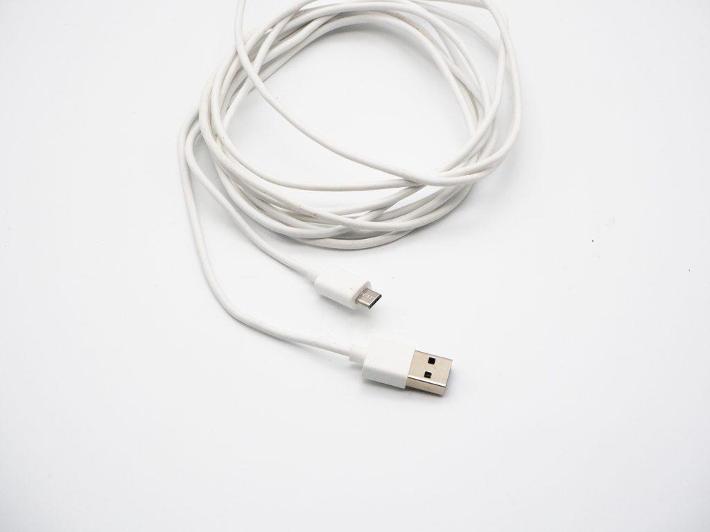 Weißes langes Kabel mit USB zusammengerollt auf weißem Grund
