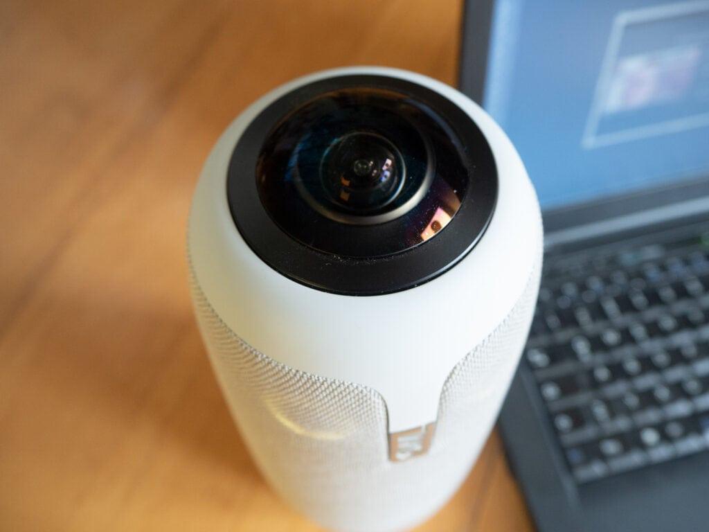 Die zylinderförmige weiße Kamera schräg von oben mit großer schwarzer Kameralinse auf Holztisch neben Notebook