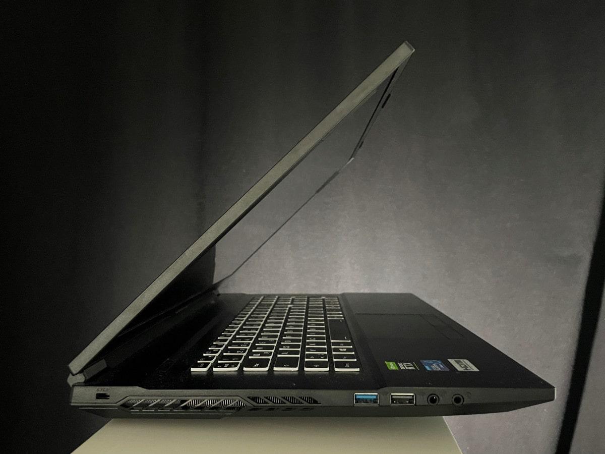 Schwarzer Laptop von der Seite leicht aufgeklappt auf weißem Podest vor schwarzem Vorhang