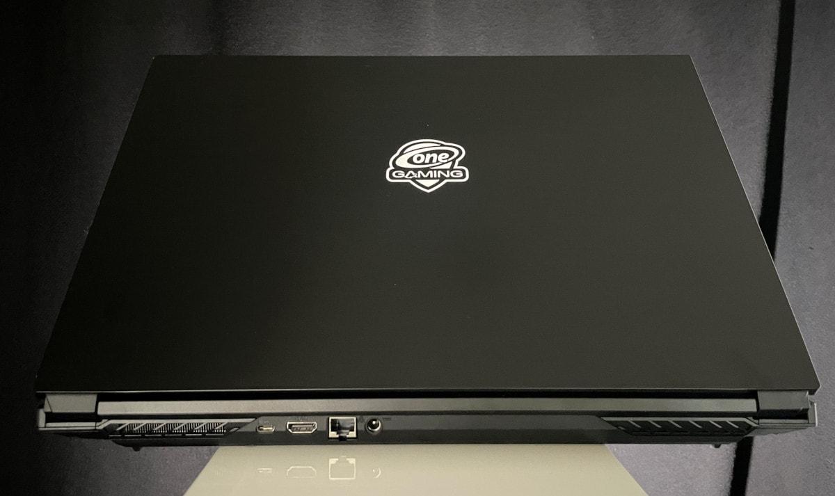 Schwarzer Laptop von hinten leicht aufgeklappt auf weißem Podest vor schwarzem Vorhang