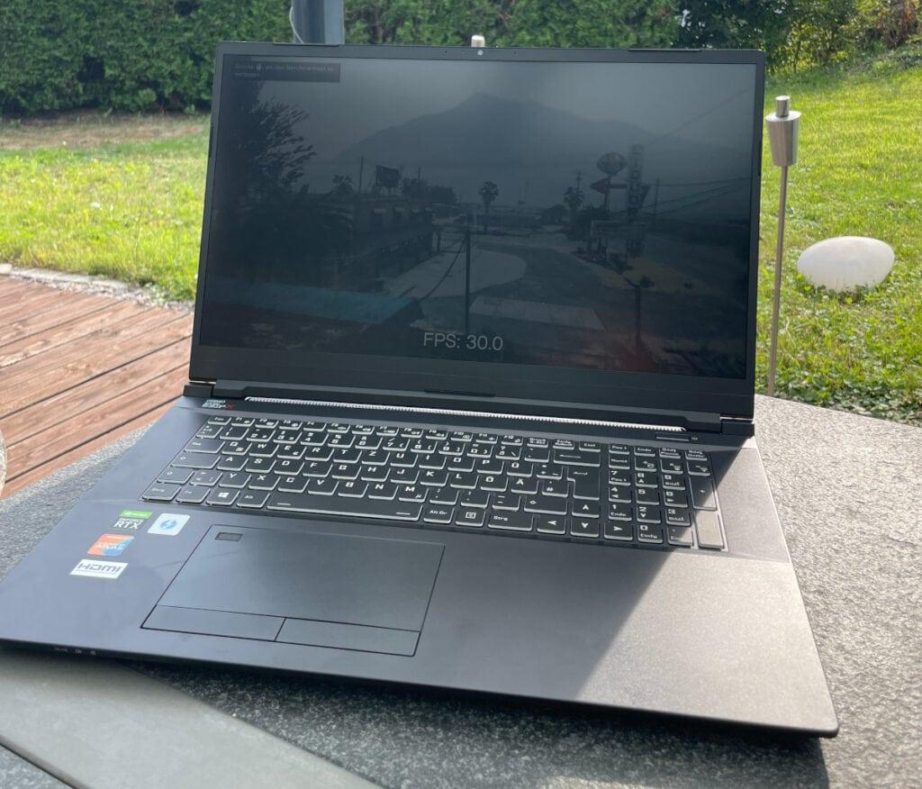 Silberner Laptop aufgeklappt schräg von vorne auf grauem Tisch vor Fensterwand