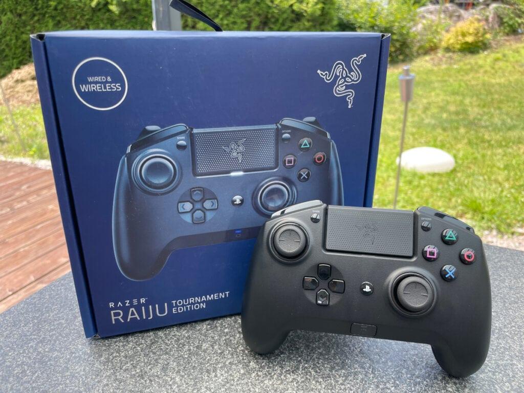 Blauer Karton aufgestellt, davor schwarzer Controller angelehnt auf grauem Tisch mit Fenstern in den Garten im Hintergrund