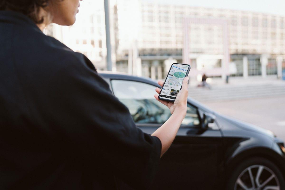Eine Frau blickt auf ein Smartphone in der Hand.