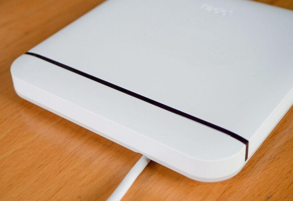 Eine Seite von weißem Gerät mit Kabel und dünnem schwarzem Streifen auf Holztisch