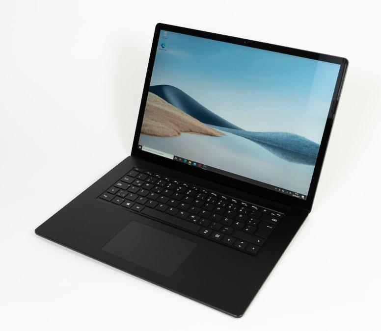 schwarzes aufgeklapptes Notebook schräg von oben mit Landschaftsbild auf weißem Hintergrund