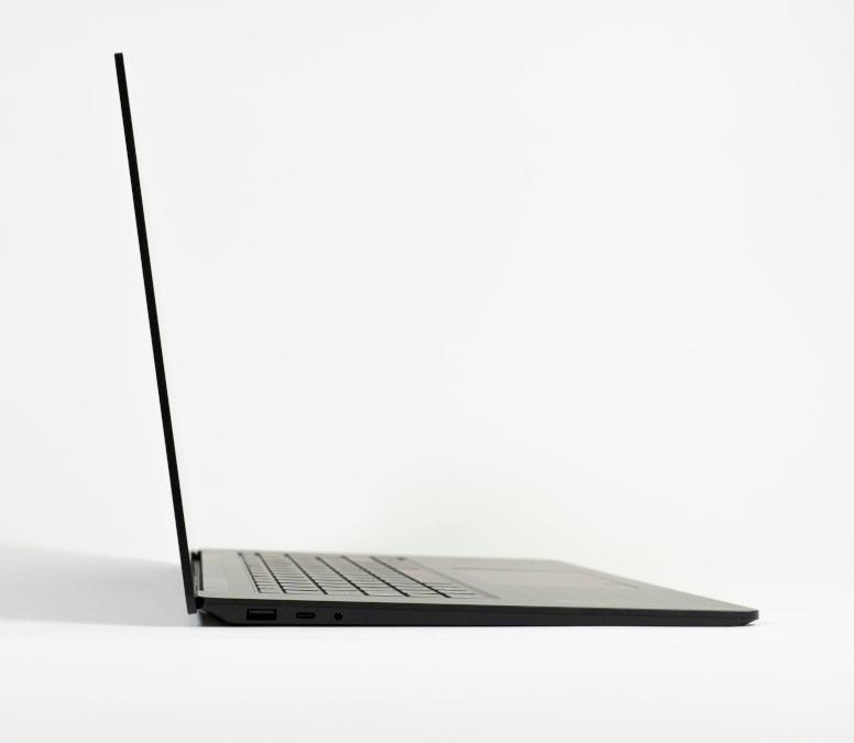 schwarzes schmales Notebook aufgeklappt von der Seite auf grauem Hintergrund