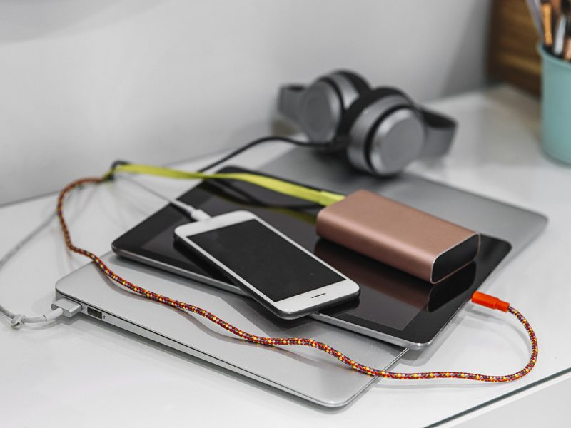Silbernes zugeklapptes Notebook auf dem weißes Smartphone, braune externe Festplatte und Kopfhörer liegen auf weißem Tisch