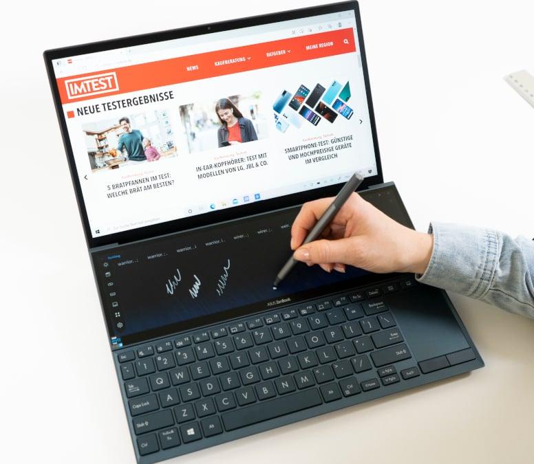 Schwarzes Notebook aufgeklappt schräg von oben, Hand die Stift bedient