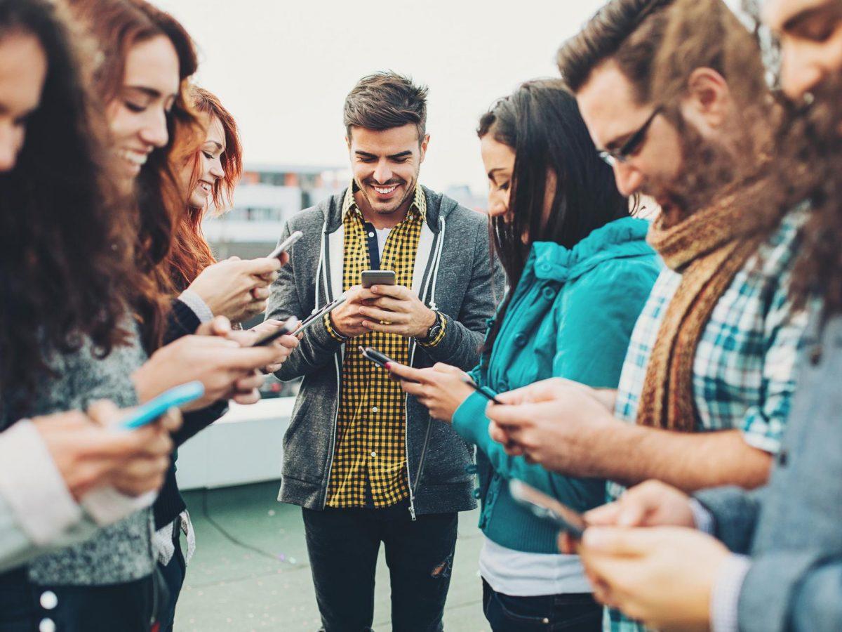 Junge Leute stehen zusammen und bedienen Smartphones