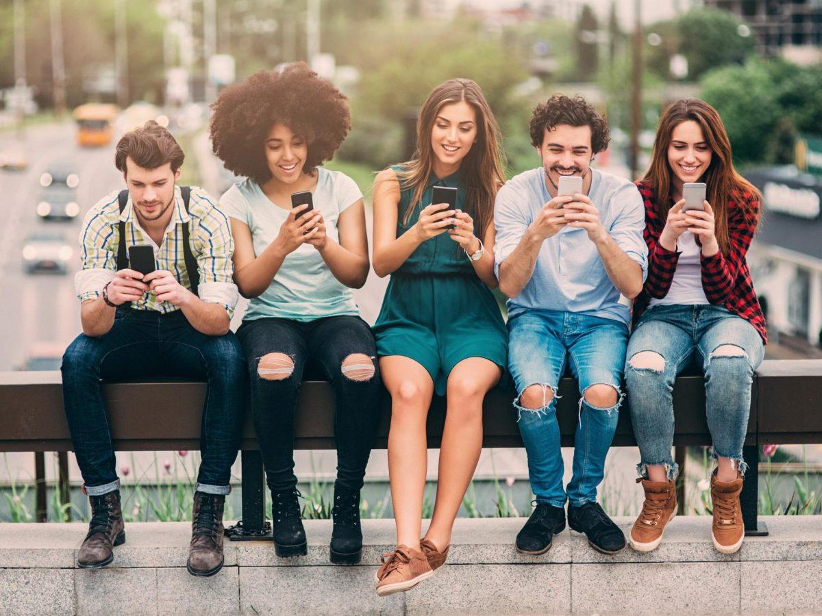 Fünf Leute sitzen auf eine Brücke und benutzen Smartphones.