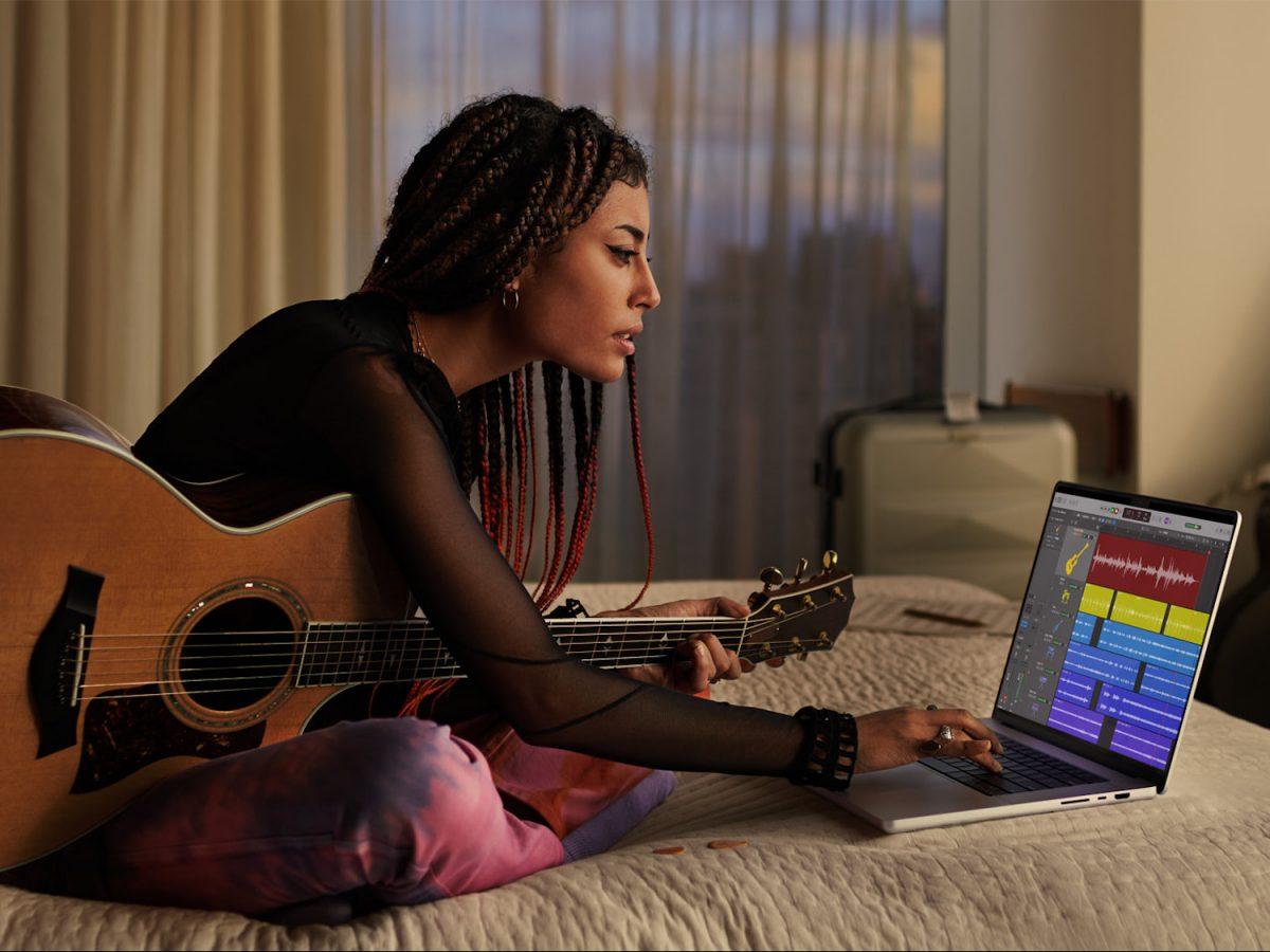 Eine Frau mit eine Gitarre sitzt vor einem MacBook