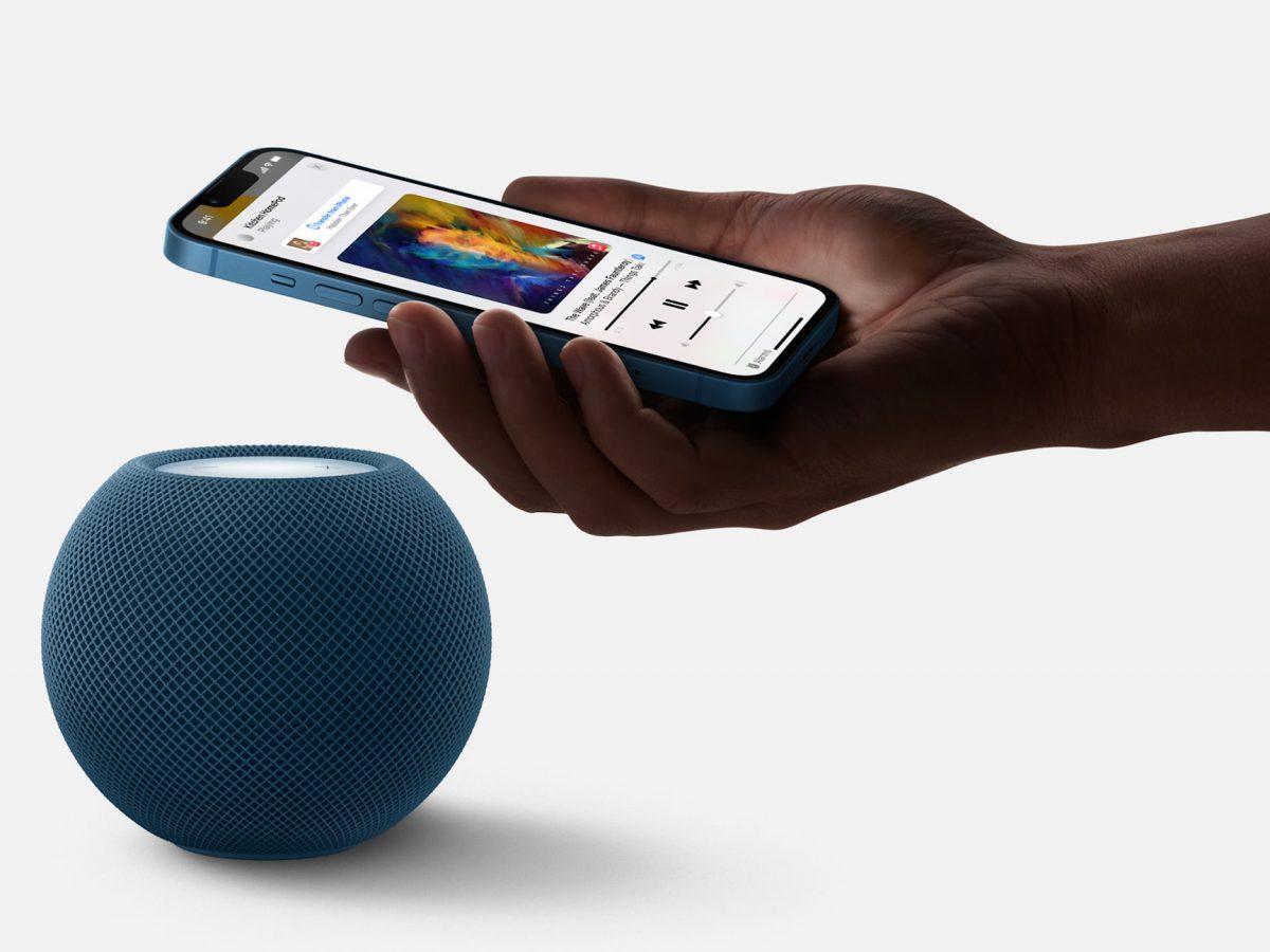 Eine Hand hält ein Smartphone vor einen HomePod mini