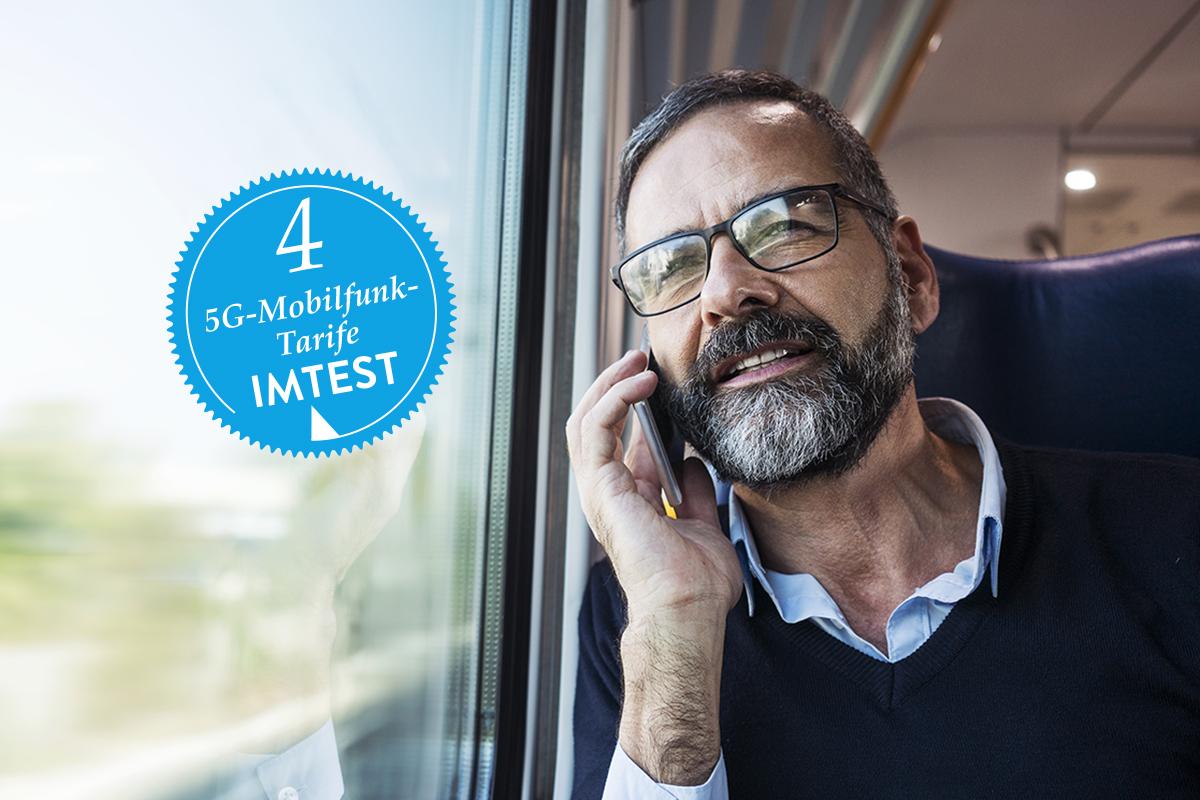 Älterer Mann mit grauem Bart und Brille sitzt im Zug am Fenster und hält sich Smartphone ans Ohr