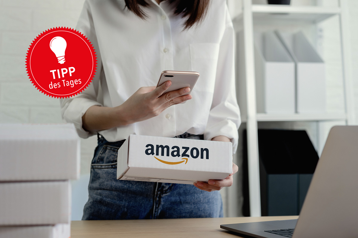 Frau mit Amazon-Paket und Smartphone in der Hand.