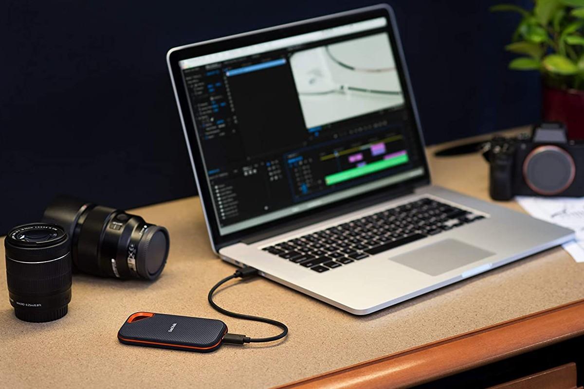 Das Bild zeigt eine SSD mit einem Laptop und einer Kamera