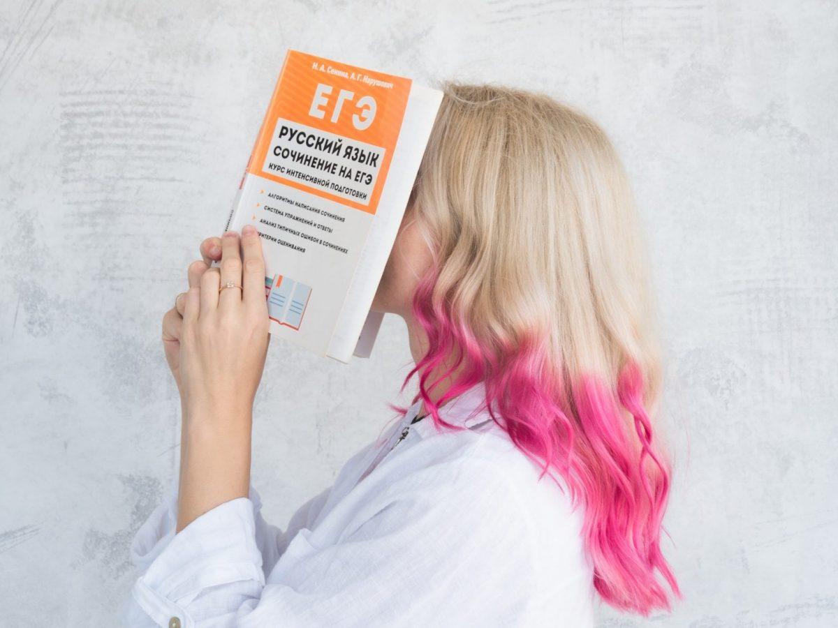 Eine Frau hält sich ein Buch vor das Gesicht